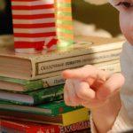 girl reading to teddy bear under the Christmas tree